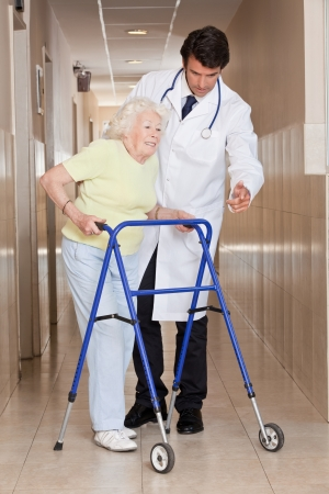 onto: A doctor assisting a senior woman onto her walker
