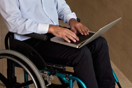 Close-up of man on wheelchair using laptop  photo