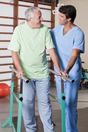f�sica: Hombre mayor con la terapia ambulatoria con su terapeuta