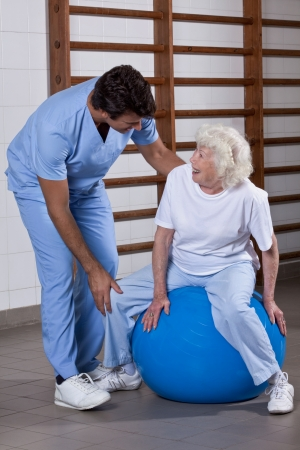 swiss ball: Male Physical therapist helping a patient  Stock Photo