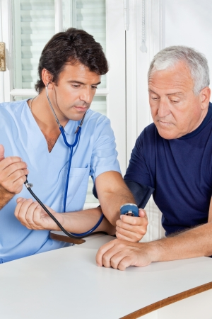 Young male nurse checking blood pressure of a senior man at hospital photo