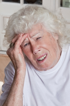 Portrait of a senior woman holding her head in pain   photo