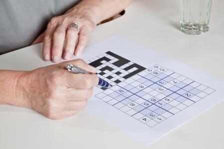 sudoku: Portrait of mature woman playing sudoku puzzle  Stock Photo