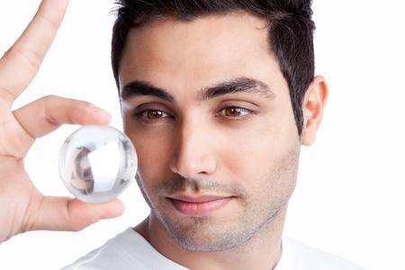 Portrait des jungen Mannes, der Kristallkugel isoliert auf weißem Hintergrund