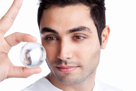 Portrait of young man holding crystal ball isolated on white background  photo