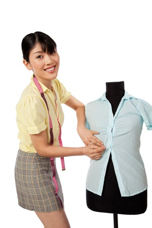 seamstress: Young Asian woman dressmaker adjusting clothes on tailoring mannequin