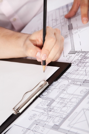 engineering drawing: Close-up of human hand with pencil over clipboard and blueprints with sketches of projects