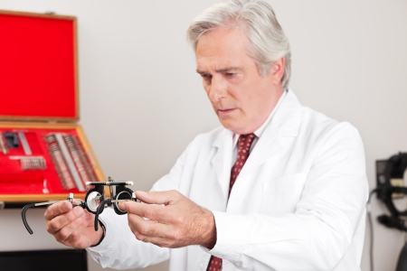 Mature optometrist examining trial frame for eye examination in the clinic photo