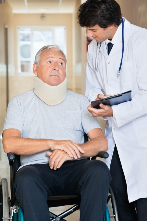 Doctor writing on clipboard while communicating with senior man sitting in wheel chair photo