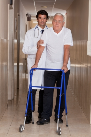 A doctor assisting a senior citizen onto his walker  photo