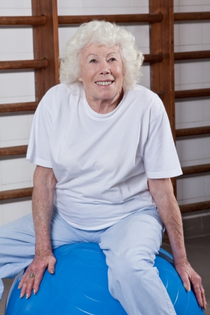 Happy Senior woman sits on a fitball  photo