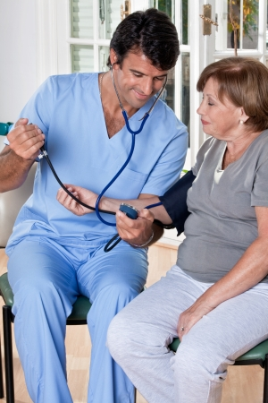 blood pressure cuff: Doctor taking the blood pressure of a patient