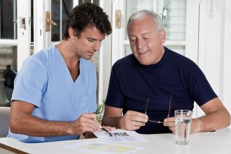 sudoku: Portrait of mature man playing sudoku puzzle  Stock Photo