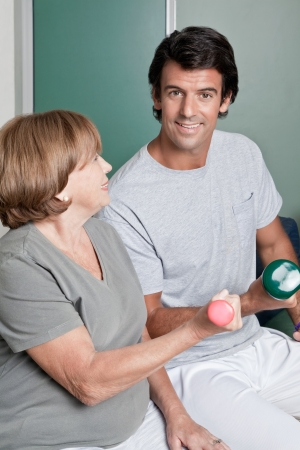 Mature woman exercising in gym with young instructor  photo