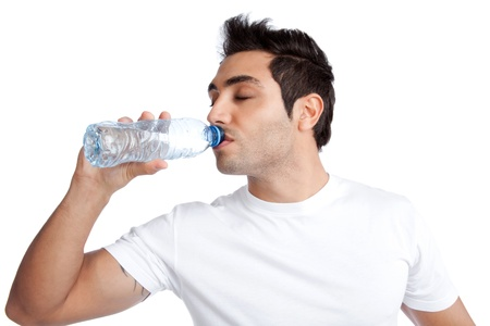 people drinking water: Portrait of young man drinking water from bottle isolated on white background