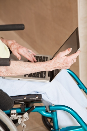 Close-up of woman on wheelchair using laptop  photo