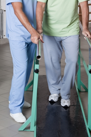 physical injury: Senior man having ambulatory therapy with his therapist