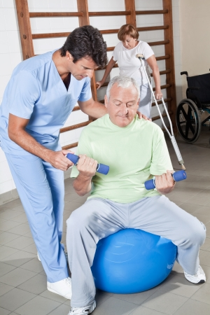 therapist: Male Physical therapist helping a patient  Stock Photo