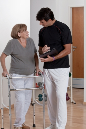 physical therapist: Patient with walker discusses his progress  Stock Photo