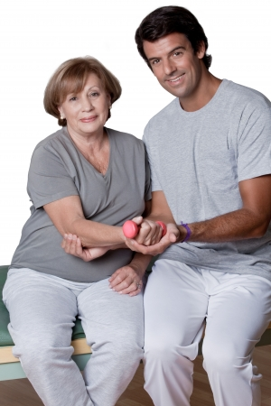 Therapist man helping woman to exercise with barbell  Stock Photo - 14287926