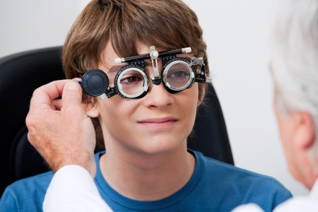 eye exam: Optometrist taking eye test through trial frames at the clinic Stock Photo