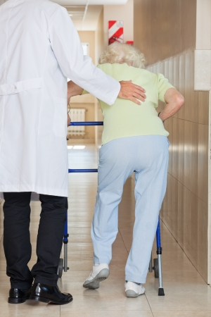 Rear view of a young doctor assisting senior woman to use walker photo