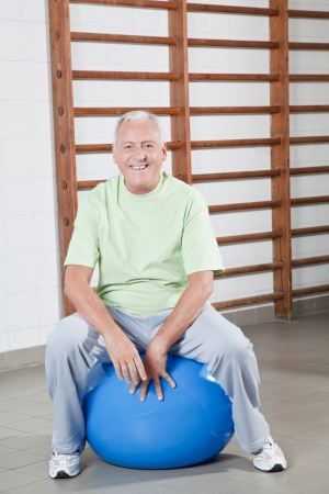 Happy Senior man sits on a fitball  photo