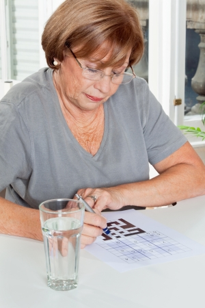 sudoku: Senior woman playing leisure games with glass of water in foreground