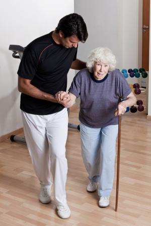 aide � la personne: Th�rapeute Aider le patient � marcher avec une canne Banque d'images