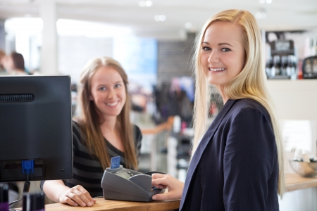 Receptionist and client in beauty salon paying with credit card
