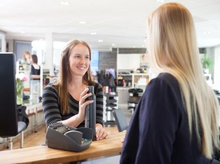 recepcionista: Recepcionista y un cliente en la tarjeta de crédito deslizando salón de belleza