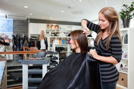 stylist: Hairdresser thinning customers hair in beauty salon  Stock Photo