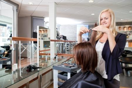hairdresser parlor: Hairdresser cutting client s hair in beauty salon