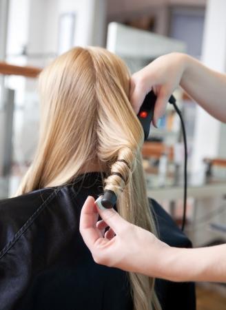 Stylist curling womans hair in beauty salon   photo