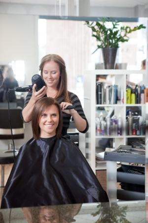 hair dryer: Estilista de la mujer de secado s de cabello en un sal�n de belleza Foto de archivo