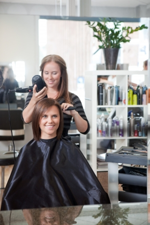 Stylist drying woman s hair in beauty salon   Stock Photo - 14350868