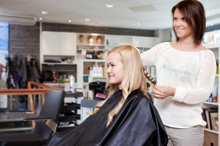 salon hair: Stylist curling womans hair in beauty salon   Stock Photo