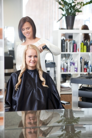 Young Female in hair salon having her hair styled photo