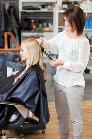 beauty parlour: Stylist curling hair of a young blond customer Stock Photo
