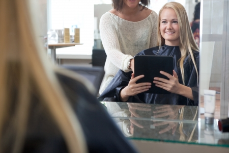 Young woman with digital tablet showing hairstyle to hair dresser photo