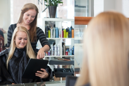 Female customer showing hair style on tablet computer Stock Photo - 14350776