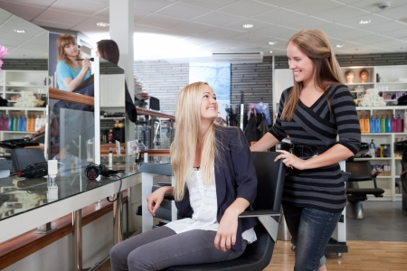 Hairdresser welcoming customer to beauty salon photo