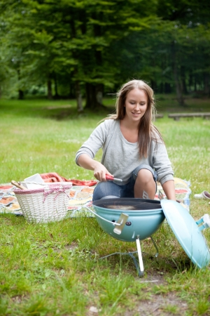 Happy young adult starting a BBQ in the park photo