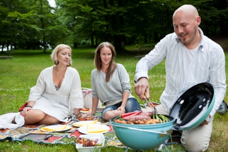 barbecue party: Group of friends barbecuing in park - shallow depth of field, focus on women