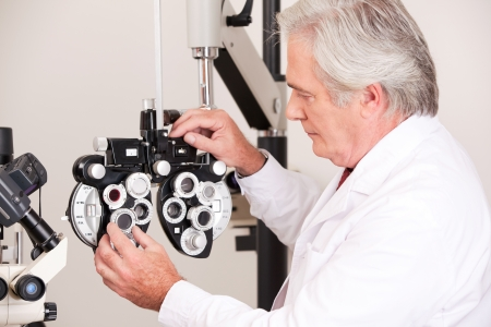 Doctor in ophthalmology clinic adjusting phoropter  photo
