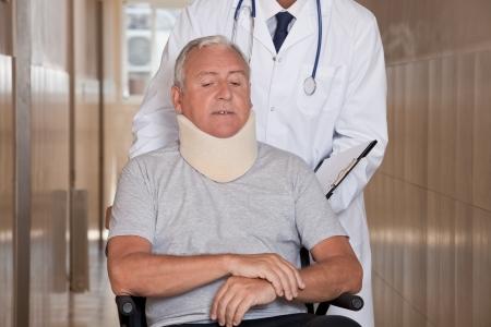lesionado: Doctor con cuello ortopédico paciente lleva en silla de ruedas