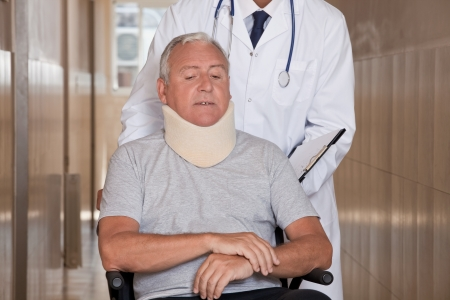 Doctor with patient wearing neck brace in wheelchair  photo