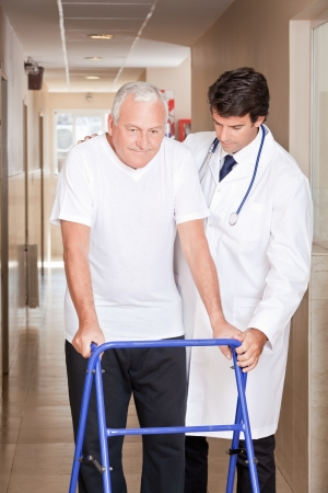 assisting: A doctor assisting a senior citizen onto his walker