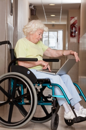 Retired woman on wheelchair using laptop  photo