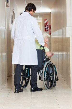 Rear view of a young doctor with senior woman sitting in wheel chair at hospital corridor photo